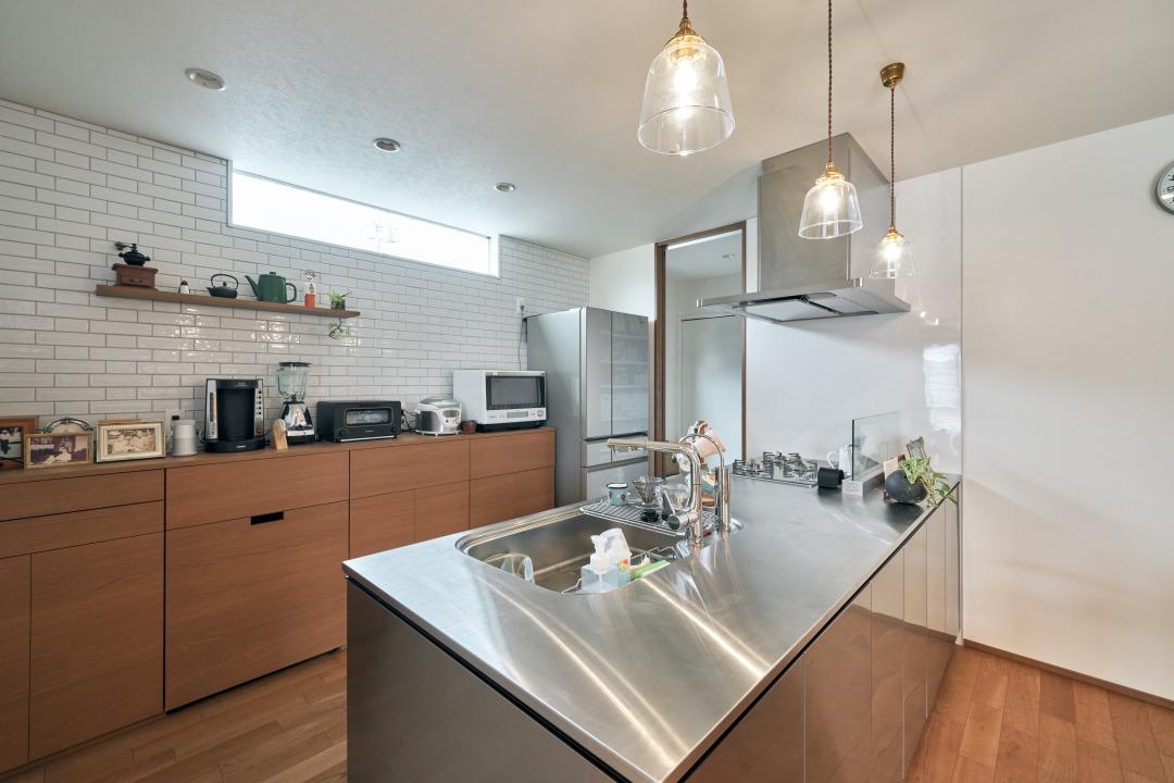 デザイン性と機能性を併せ持つオールステンレスキッチン。キッチン~洗面~浴室と一直線につながる動線も確保。背面の造作収納など、自分好みの空間づくりを意識した。