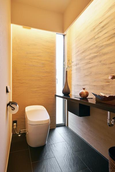 天然素材のような凹凸の陰影がトイレ空間までもスタイリッシュに昇華する。