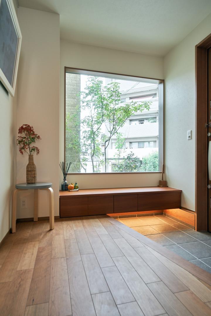 玄関横に大きく取ったFIX窓は玄関を明るく照らし、四季の移ろいを感じることができる、自然のギャラリーに。開口部を大きくするためにシューズケースはベンチタイプを採用。