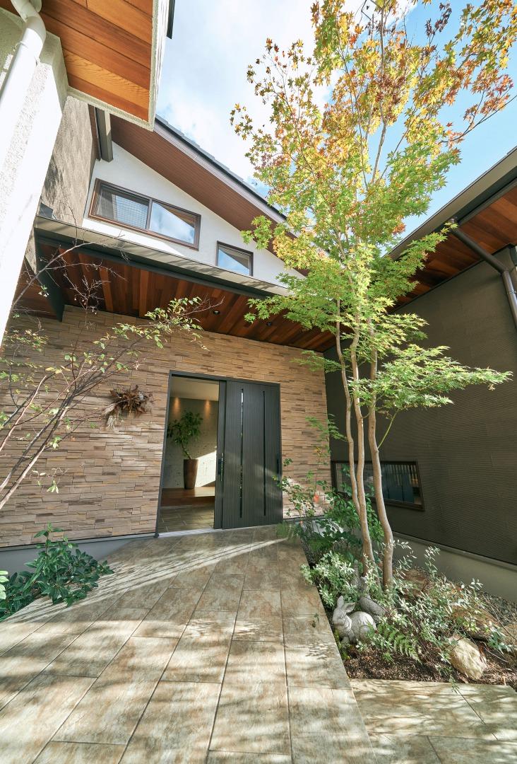 季節の木々と花々がそよぐ中、歩を進めると、三州瓦の片流れ屋根と彫りの深い石壁が陰影を醸す。