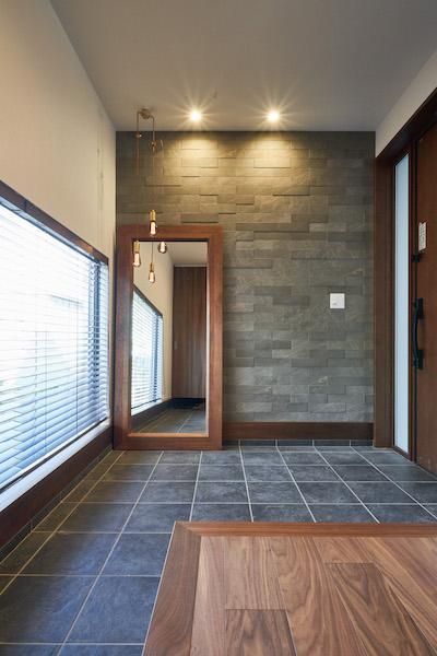 壁面タイルや照明、ミラーが、玄関から迎え入れるお客様をそっともてなします。L型の玄関框も印象的です。