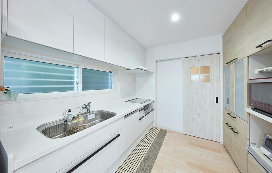 """キッチンもレンジフードもすべてホワイトカラーで統一。 引出しなど""""隠せる""""収納を多く配置することで家事の負担を軽減。"""