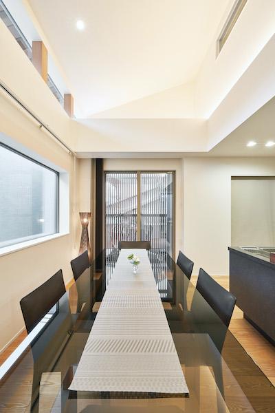 勾配天井を利用した吹き抜けのあるダイニング。自然光が降り注ぐ爽やかな食卓。