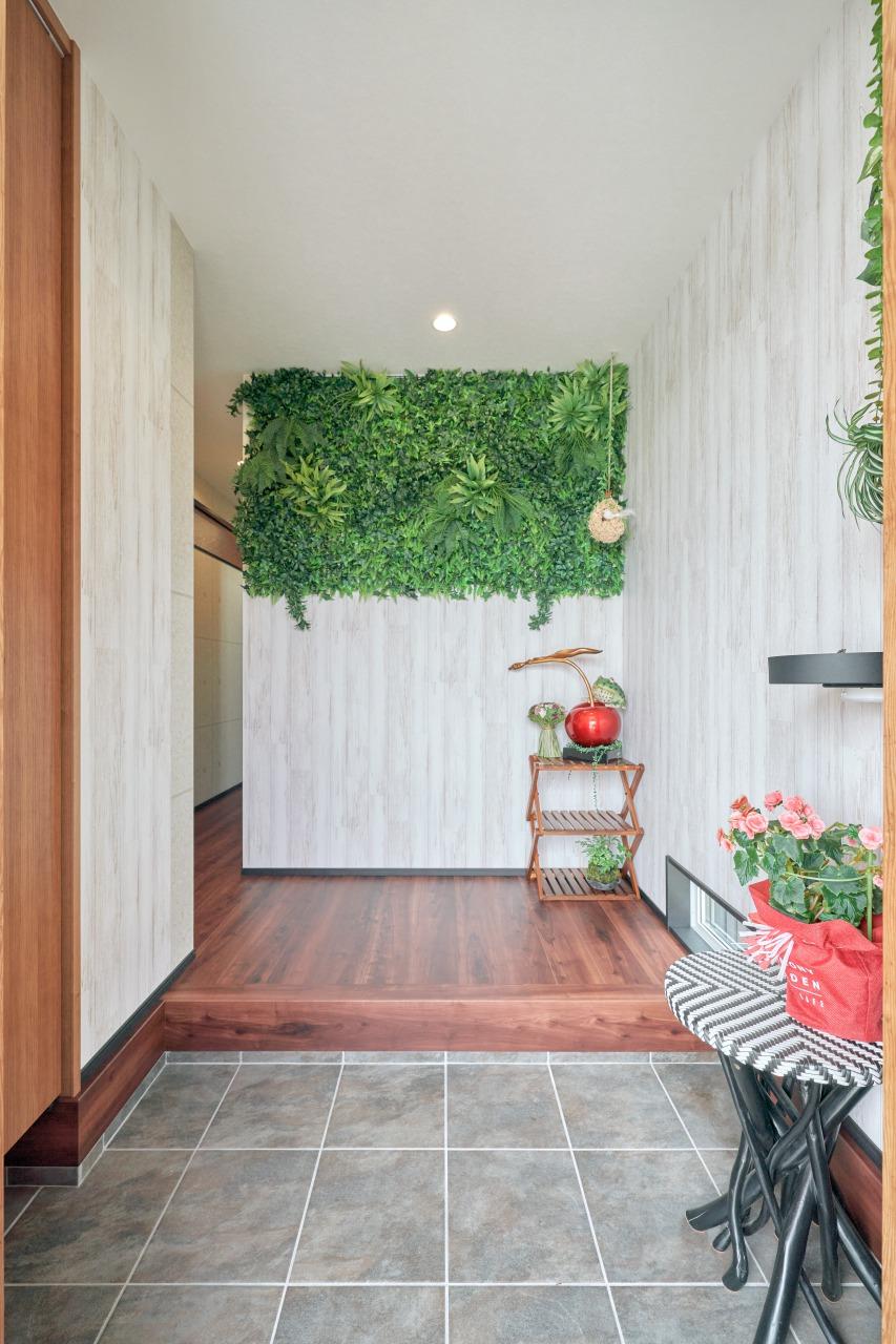 玄関正面には大きなフェイクグリーンを配置し、訪れた人を出迎える。白木目の壁紙も優しさと落ち着きを感じさせてくれる。