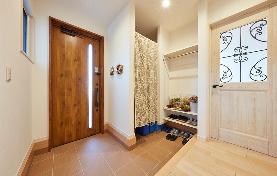 帰宅時に傘やコートを室内に入れずに片付けられる土間収納を設置した玄関スペース。 来客には目が触れないように配置を工夫。